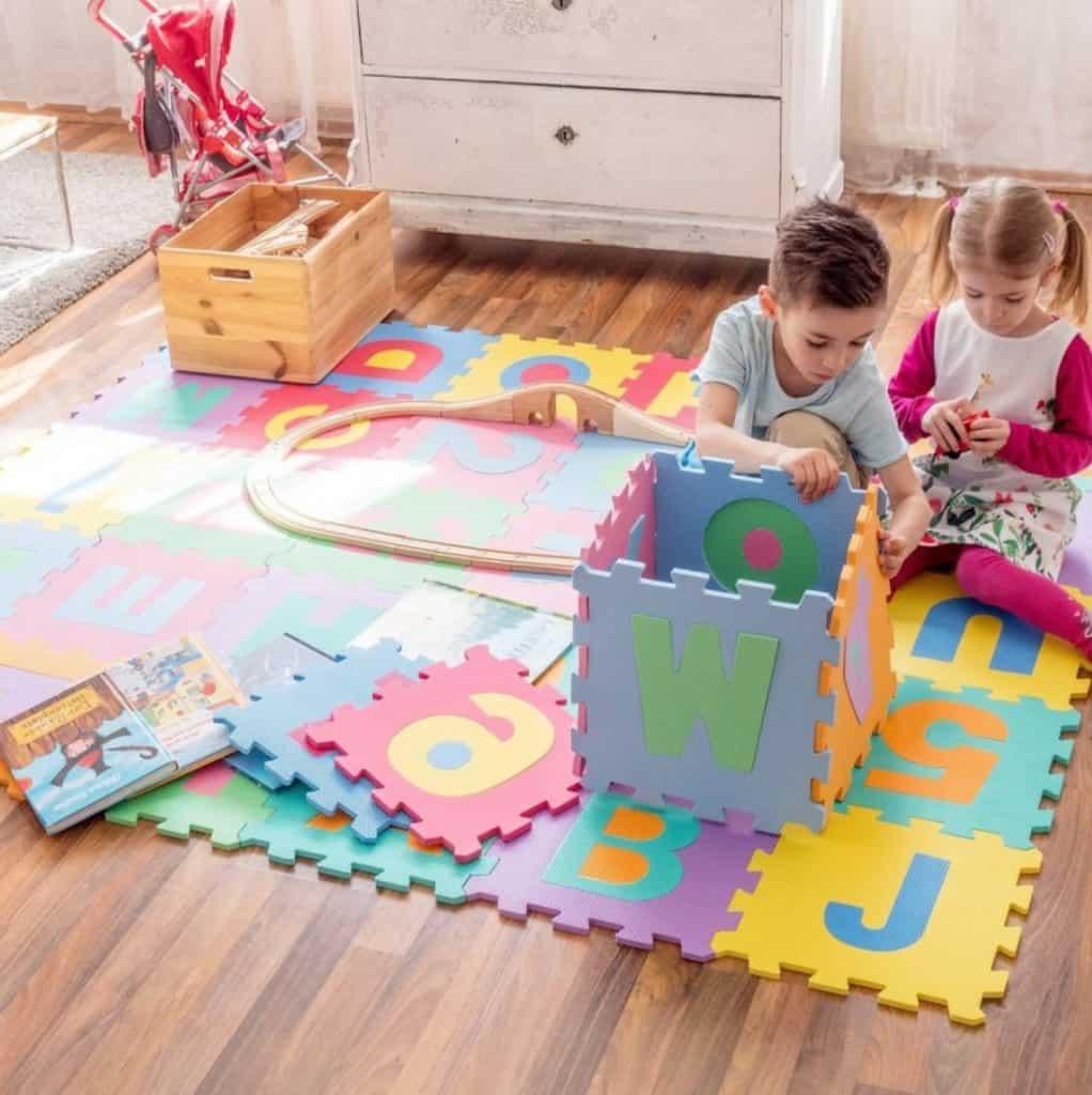 Barn bygger med pusselmattor.