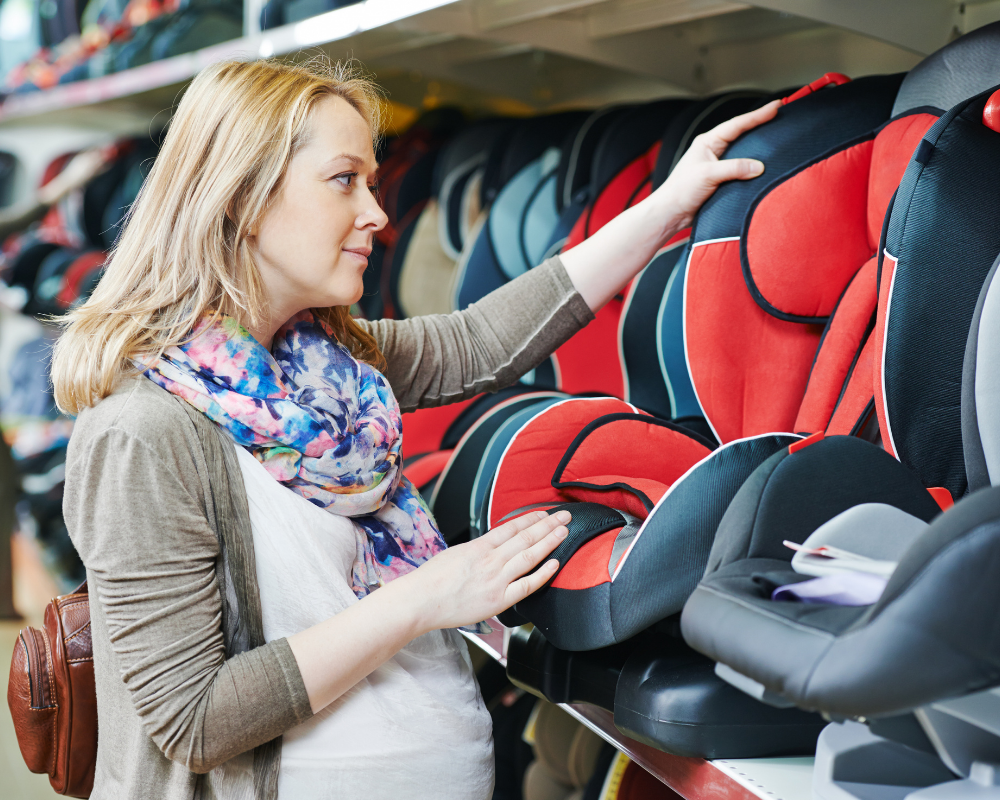 Kvinna i butik som tittar på bilbarnstolar på en hylla.