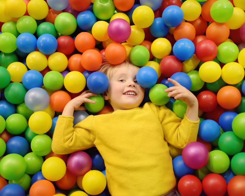 Barn med gul tröja i bollhav med bollar i många olika färger.