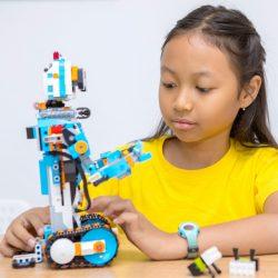 Barn med gul t-shirt leker med Lego-robot