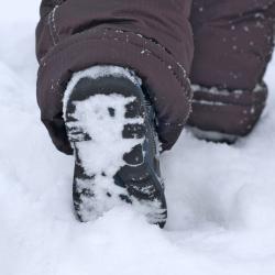 Barnfot med vintersko promenerar i snön i närbild