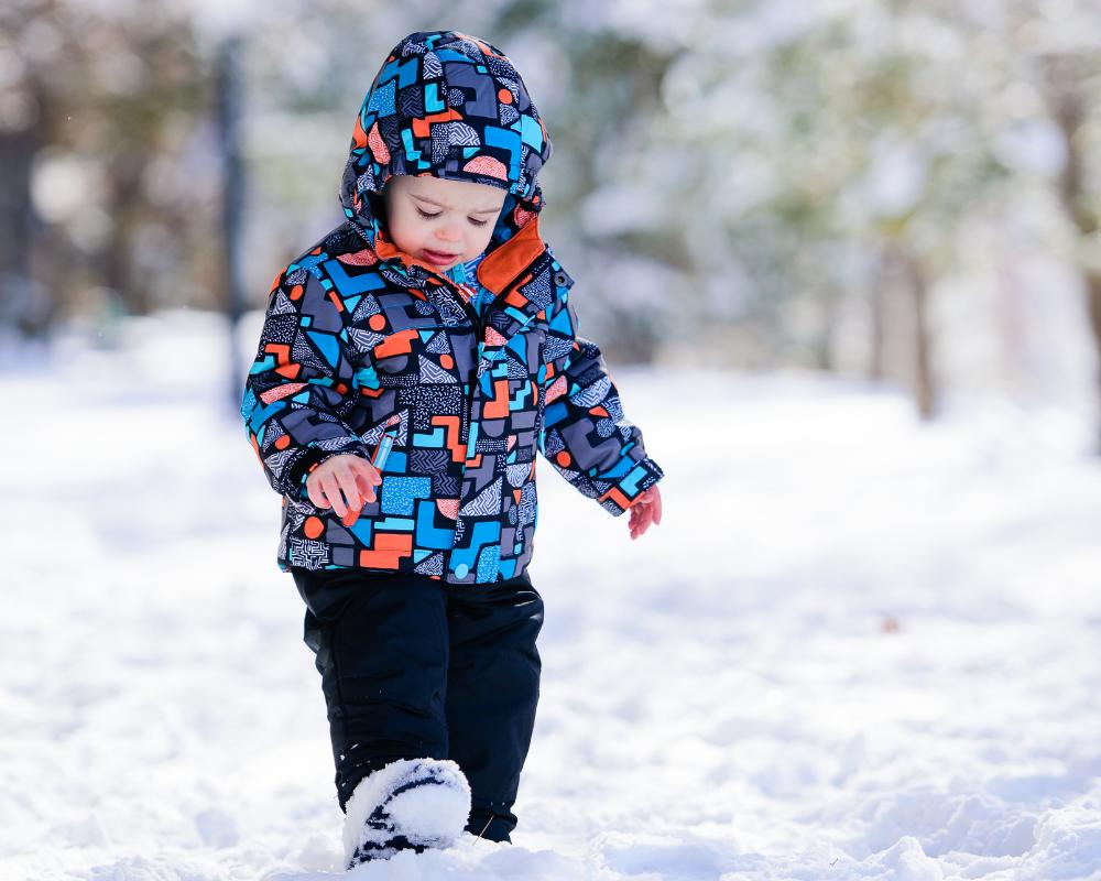Litet barn med vinterskor och jacka i vinterlandskap med snö.