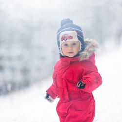 Barn med röd vinteroverall i vinterlandskap