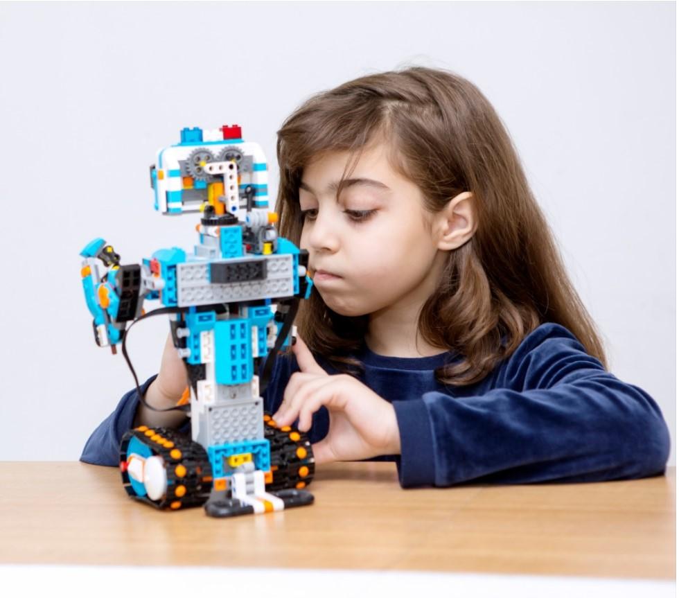 Flicka vid bord med lego-robot