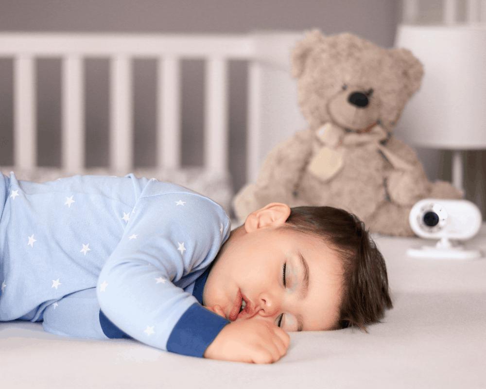 Spädbarn sover i spjälsäng med en babyvakt i bakgrunden