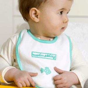 Barn med vit och grön haklapp