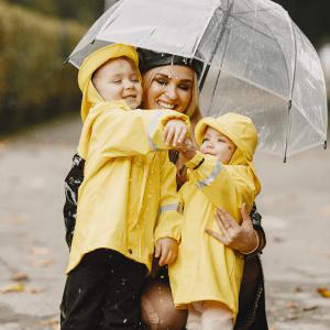 Mamma med två barn under paraply. Barnen har gula regnkläder.
