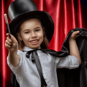 Liten flick utklädd till trollkarl redo att leka med trollerilåda