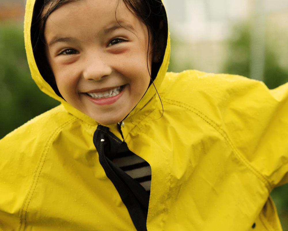Barn skrattar i regnet med gul regnjacka