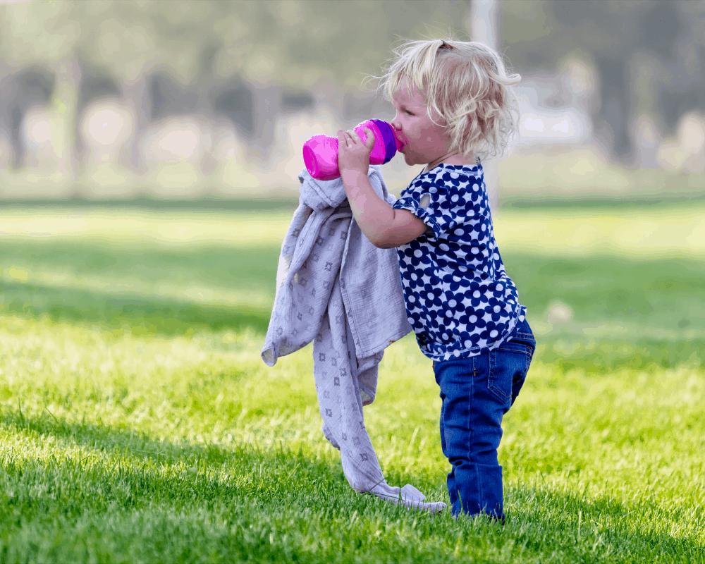 Flicka står på gräsmatta och dricker ur en rosa vattenflaska.