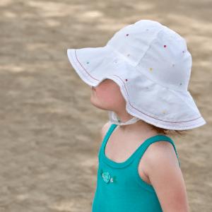 Flick med vit solhatt på stranden