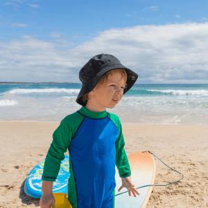 Barn med UV-dräkt och solhatt på stranden