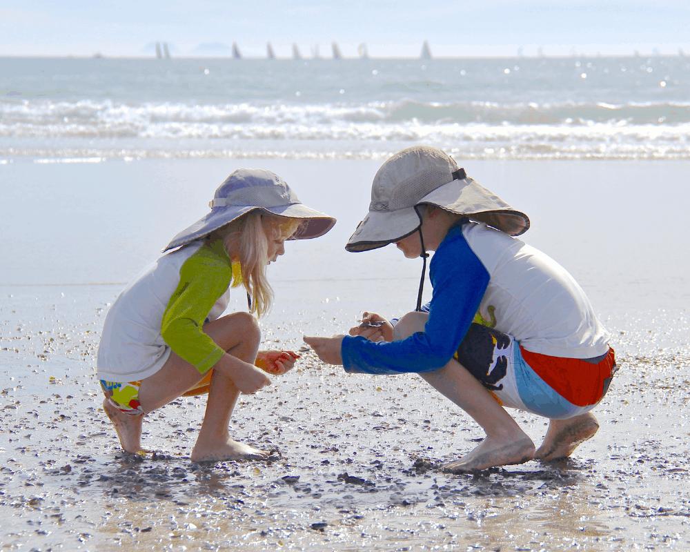 Två barn med UV-kläder och solhatt leker på stranden
