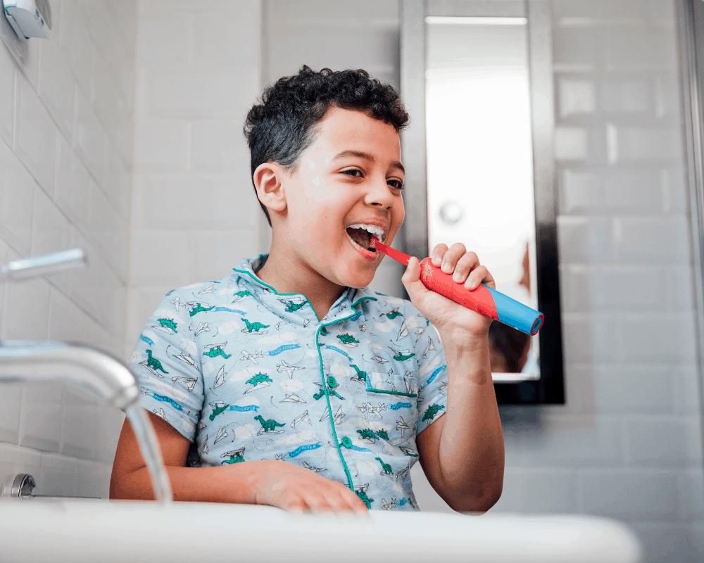 Pojke borstar tänderna med eltandborste för barn