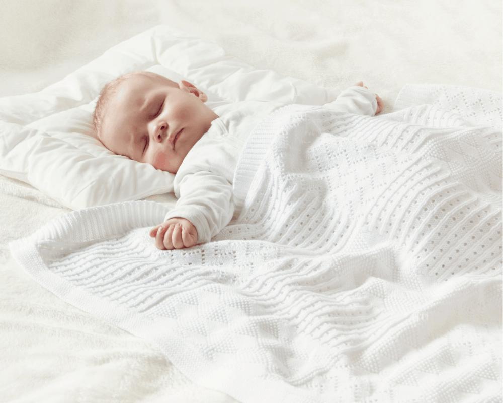 Bebis sover med huvudet på kudde